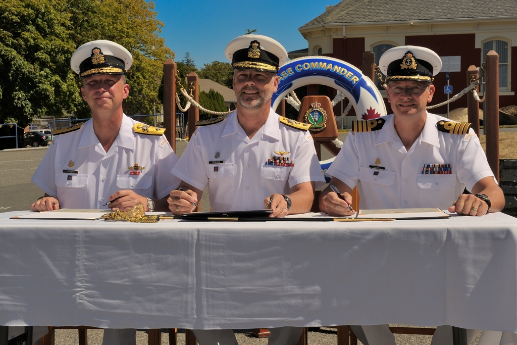 Outgoing CFB Esquimalt Base Commander Cmdre Luc Cassivi (left), RAdm Bill Truelove and incoming Base Commander Capt(N) Steve Waddel (right) sign Change of Command documents at CFB Esquimalt on July 30, 2014.